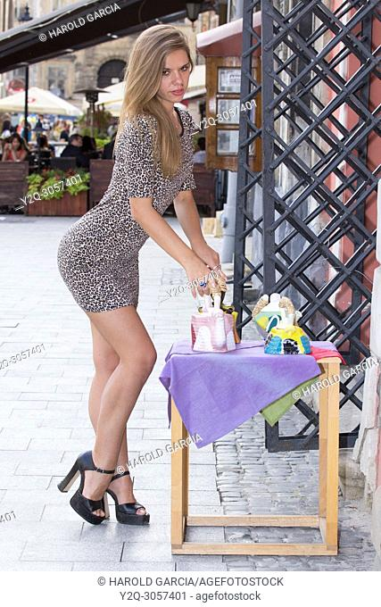 Sexy Ukrainian woman wearing a leopard skin print dress posing on the street with a tea pot for a photographic sequence in the ancient city of Lviv, Ukraine