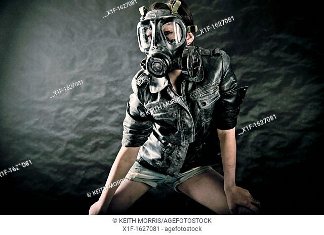 A young cyber punk steam punk girl woman wearing a leather jacket and gas mask in a photo studio