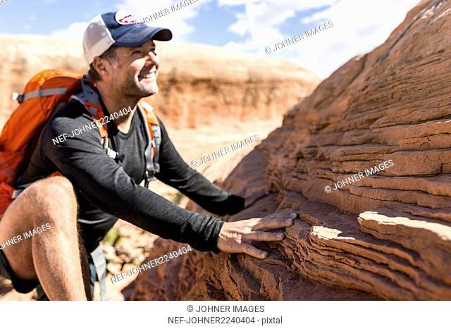 Smiling man climbing rock