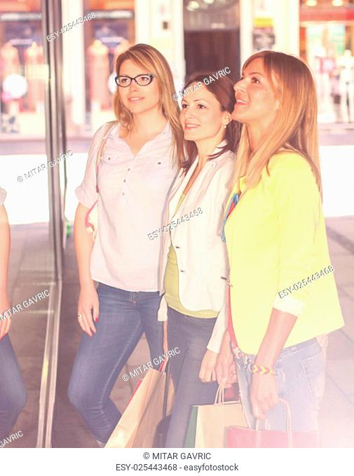 Shopping Girlfriends looking at shop window on the street