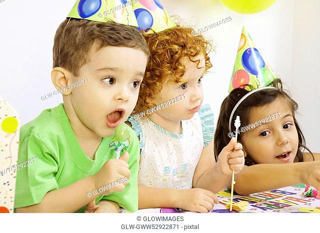 Two girls and a boy at a birthday party