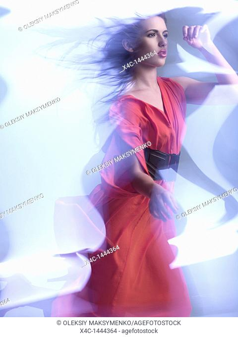Futuristic dynamic high fashion photo of a young woman wearing a red dress in shiny neon light settings  The photo has a slight motion blur due to its nature...