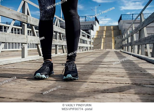 Legs of athletic woman standing on a pier