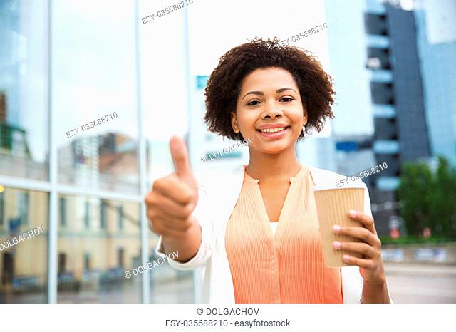 business, drinks, gesture and people concept - young smiling african american businesswoman with coffee cup in city showing thumbs up