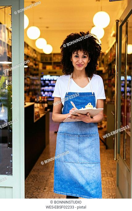 Portrait of smiling woman with clipboard standing in entrance door of a store