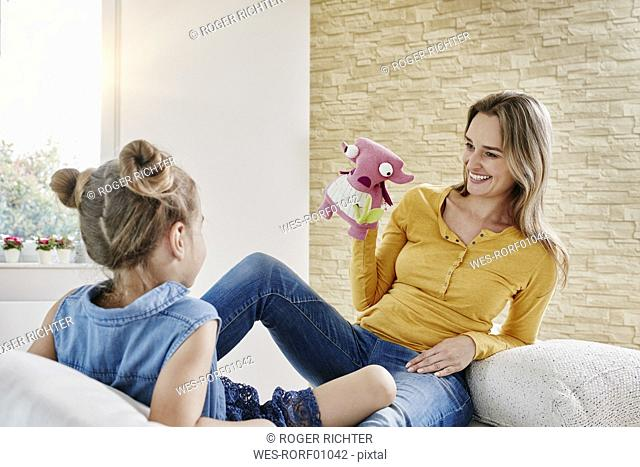 Happy mother and daughter playing with cuddly toy at home