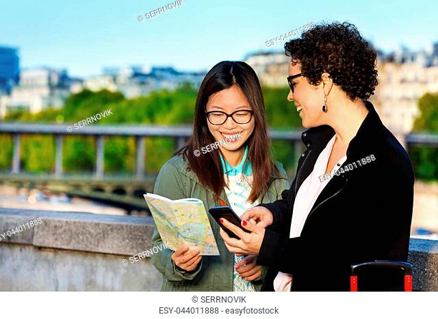 Two women tourists holding a paper map and smart phone standing at the embankment of the Seine River