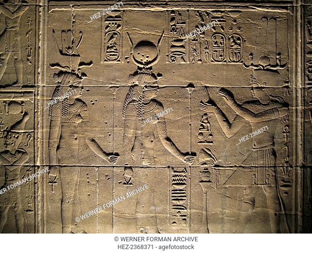 Relief depicting a pharaoh making offerings to the goddesses Isis and Hathor, Philae, Egypt. The construction of the temple dedicated to the Ancient Egyptian...