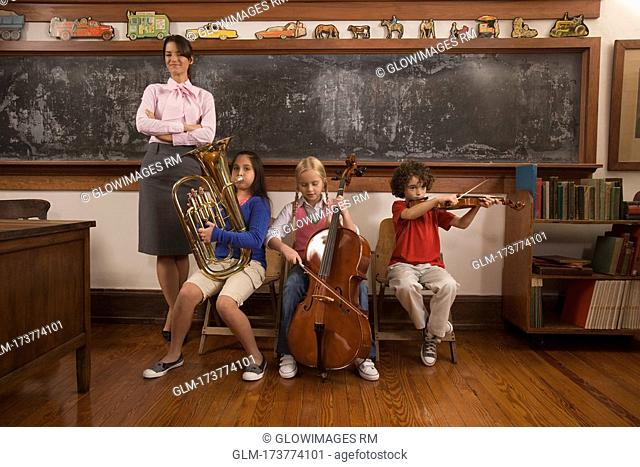 Students playing musical instruments with their teacher standing beside them
