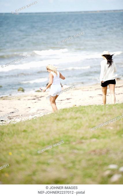 Two young women walking on beach