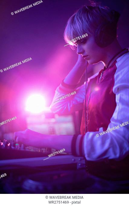 Female dj listening to headphones while playing music