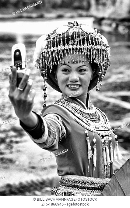 Local woman in traditional costume taking camera cell phone portrait in Guilin Yangshuo area of China