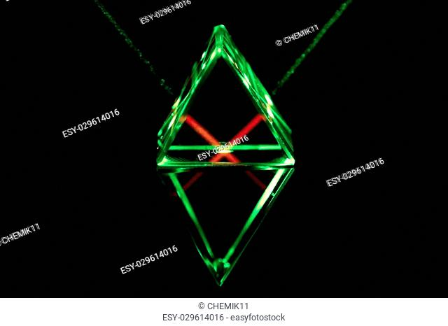 Green laser rays pass through and reflect inside the glass prism
