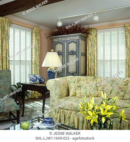 LIVING ROOM - Yellow floral print sofa, pale peach walls, Queen Anne side table, tall blue and white painted armoire with red foliage on top