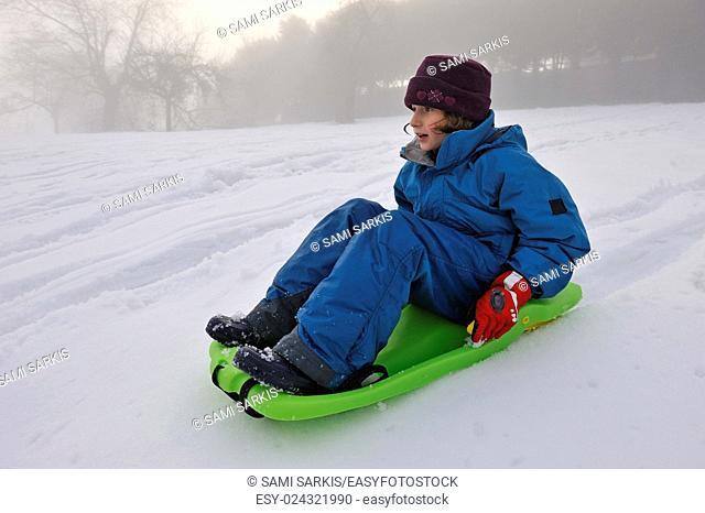 Little girl sledging in a winter landscape
