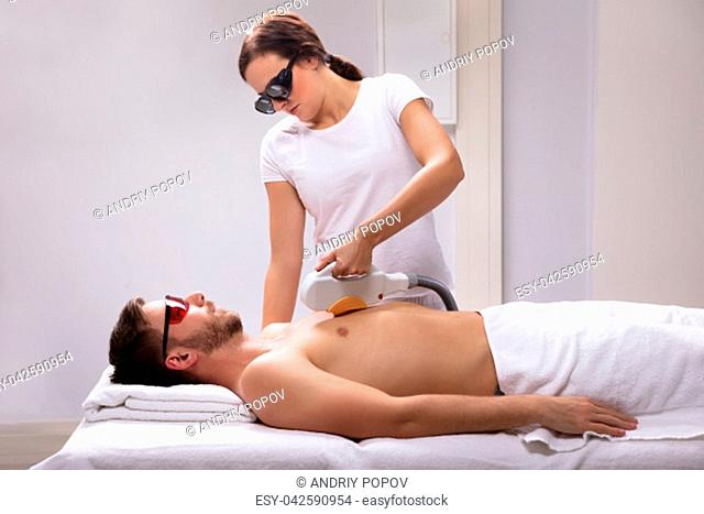 Young Female Beautician Giving Laser Depilation Treatment On Relaxed Man's Chest