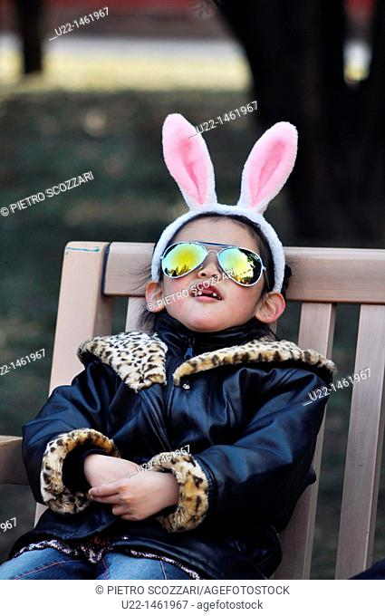 Beijing (China): a girl with sunglasses and bunny ears - in occasion of the Rabbit New Year - during the Spring Festival in Ditan Park