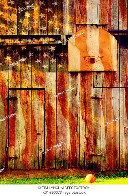 Warm light on basketball net on barn with US flag