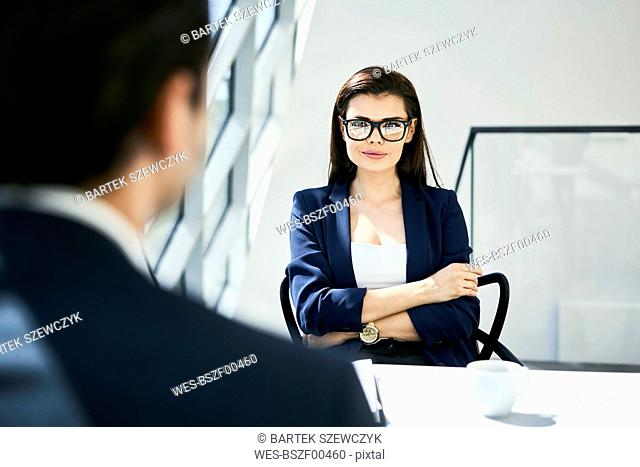 Portrait of confident businesswoman with businessman in modern office