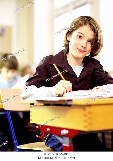 Boy sitting in his school bench