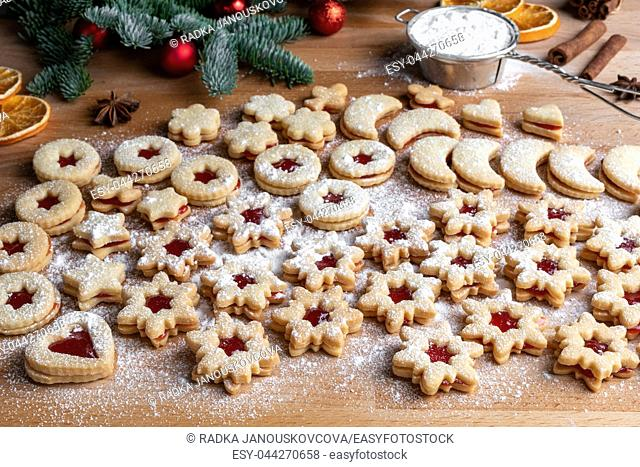 Preparation of traditional Linzer Christmas cookies with strawberry marmalade