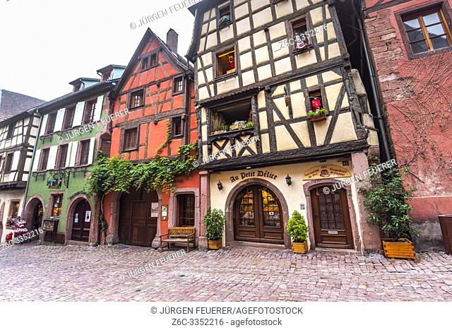 colorful house facades in the village Riquewihr, Alsace Wine Route, France, decoration with vine and antiques