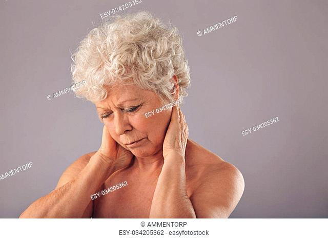 Portrait of senior woman rubbing her sore neck against grey background. Old woman suffering from neck. Discomfort with sore neck