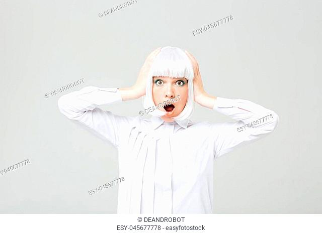 Amazed shocked young woman in blonde wig with hands on head