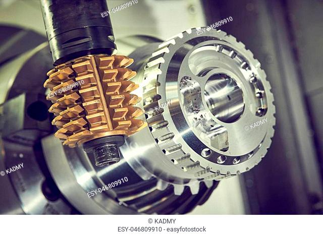 milling metalworking process. Industrial CNC machining of tooth gear by vertical hobbing cutter mill