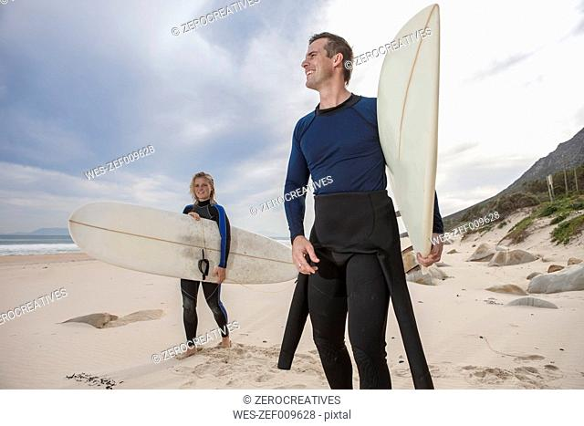 Couple with surfboards on the beach