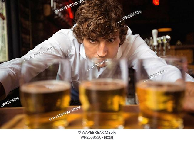 Bartender lining whisky shot glasses on bar counter