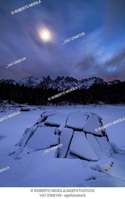 Full moon at Lake Carezza in the background the Latemar group. Ega Valley. Dolomites. Trentino Alto Adige Italy