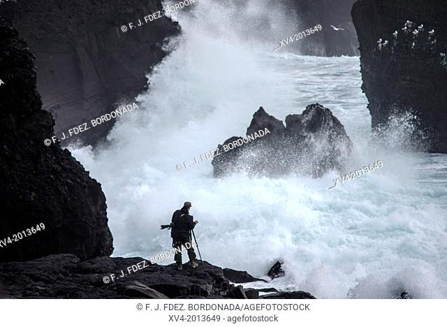 Photographer taking pictures at Reykjanesta cliffs, Southern Iceland