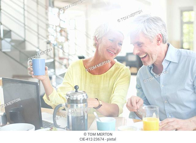Older couple laughing together at breakfast table with laptop