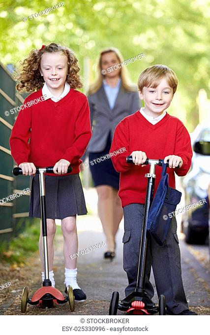 Children Riding Scooters On Their Way To School With Mother