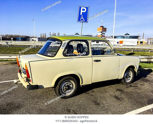Rotterdam, Netherlands. Old fashioned East-German Trabant car on tour through the industrial Maasvlakte & 2nd Maasvlakte, enjoying a sunny saturday