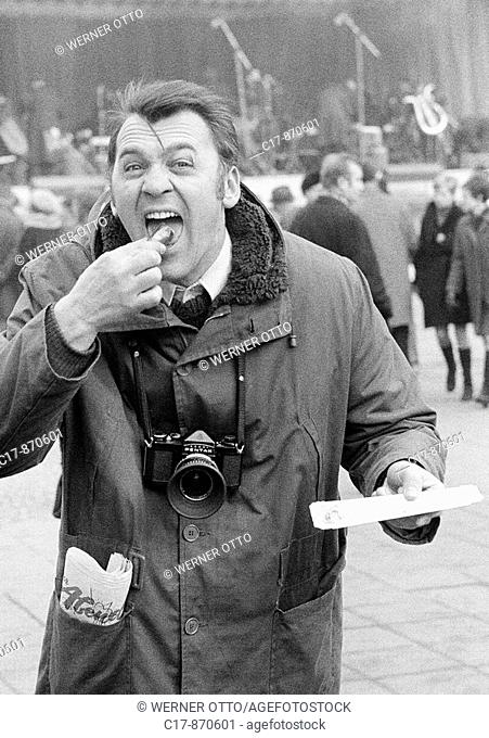 Sixties, black and white photo, people, humour, man with a camera and wide opened mouth bites into a frying sausage and makes faces, aged 30 to 35 years