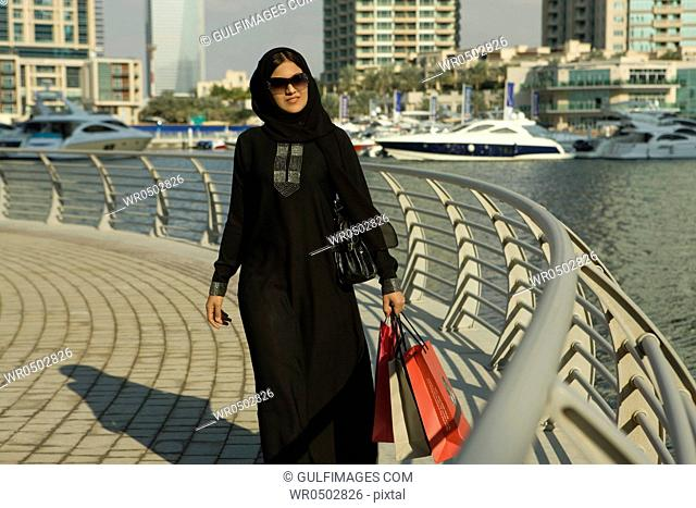 Arab woman with shopping bags, walking at Dubai Marina, UAE