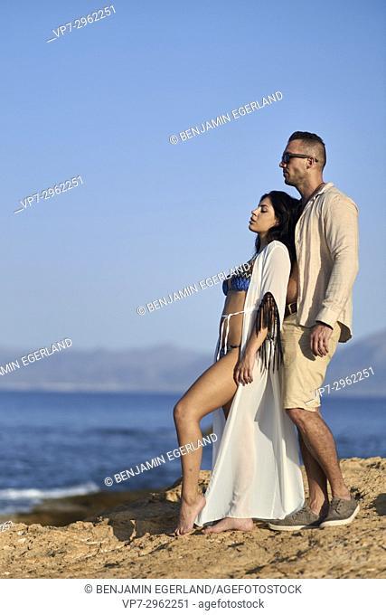 sensual woman leaning at boyfriend, enjoying in evening sun at Mediterranean beach. Greek ethnicity. In holiday destination Hersonissos, Crete, Greece
