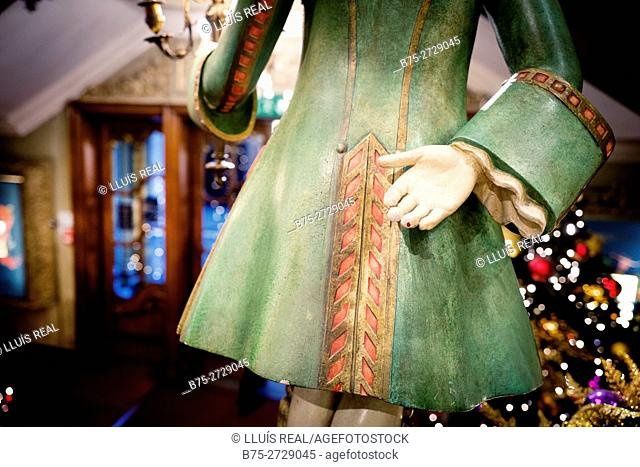 Rear view detail of English period servant figure, green, wood carving. London, England