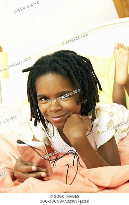 Young African girl listening to an mp3 player in bed