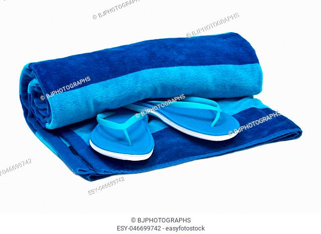 Blue cotton beach towel and flip flops isolated on white background