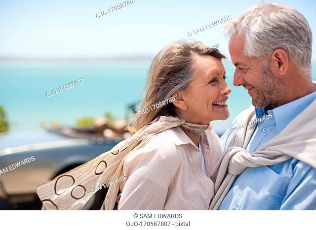 Mature couple hugging at waterfront