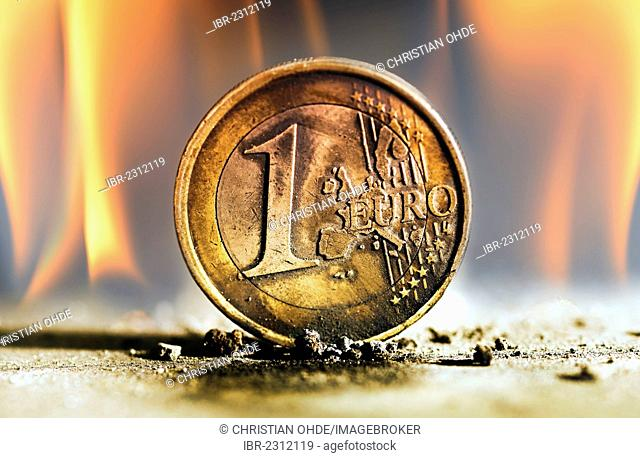 1 euro coin surrounded by fire, symbolic image for the euro crisis