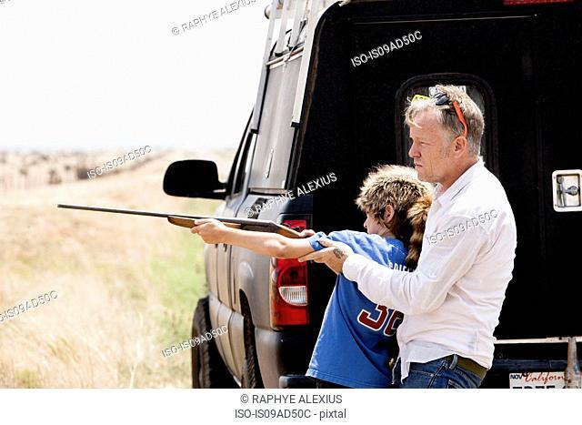 Father teaching son with rifle, Texas, USA