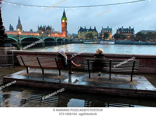 Women sitting and view of the Houses of Parliament, Westminster Bridge and The River Thames, London, England
