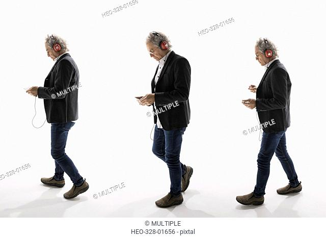 Sequence senior businessman listening to music with headphones and mp3 player against white background