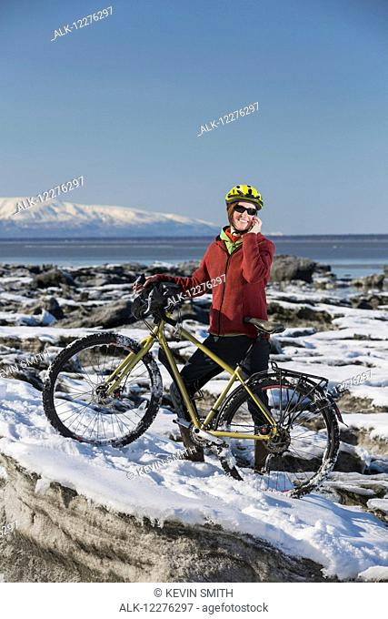 A young woman stands with her bicycle on ice while talking on a cell phone next to the Tony Knowles Coastal Trail, Anchorage, Southcentral Alaska, USA