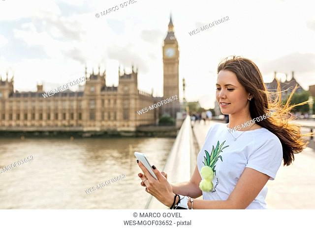 UK, London, woman sending messages with her smartphone on Westminster Bridge