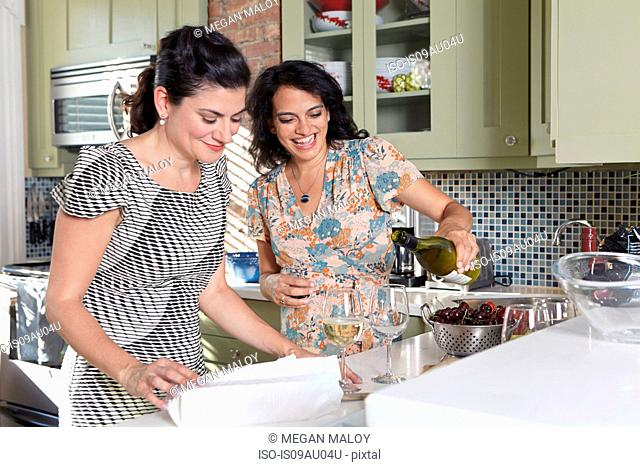 Two female friends pouring white wine in kitchen